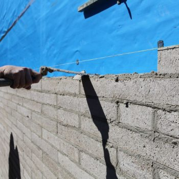 Image is of Gold Coast Pro Bricklayers working on a brick fence